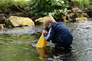 Under utan. Lasse Mildh använder en vattenkikare för att se vad som finns under vattenytan.