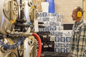 Pär Ramqvist vid 1000-liters tankarna. Det klirrande ljudet i produktionslokalen från flaskorna är högt och tröttsamt, därför har de som jobbar hörselskydd.