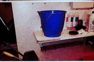 Hink som används för att samla vatten från en takläcka som inte åtgärdats trots påstötning i flera års tid.