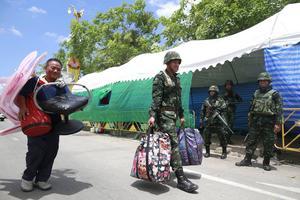 En thailändsk soldat hjälper en regeringsvänlig demonstrant vid avstädning av en protestplats i Bangkoks utkanter. Foto: AP Wason Wanichakorn