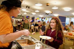 Christina Wagenius serverar lokal skolmat till Lavin Jahia.
