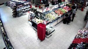 Vid fruktdisken i en matbutik flyttar männen varor från en kundkorg till en väska. Bild ur polisens förundersökning.