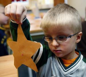 Förskolläraren hjälper till att sätta en guldtråd genom stjärnan så att den kan hängas upp.