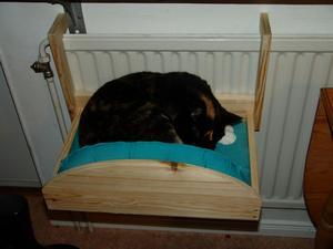 Här i elementvärmen trivs vår katt Freddie, speciellt när det är regn och rusk ute och tassarna blivit kalla. Bädden är specialkonstruerad av husse.