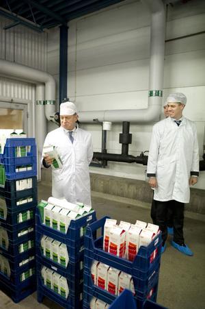 Frank Fiskers inspekterar ett mjölkpaket medan Magnus Johansson tittar på.