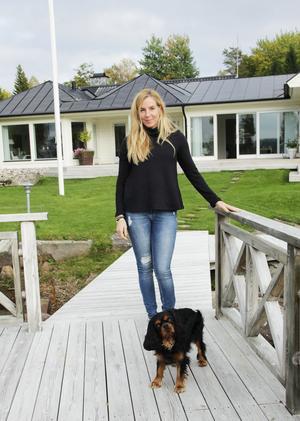 Maria Nordlander med hunden Zigge på husets baksida, som vetter mot Storsjön i området med det bibliska namnet: Heliga landet: