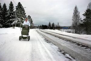 """AUTOBAHN. Här, längs väg 548 mellan Ockelbo och Åmot, promenerar Charlotta Krantz med dottern Julie, 1 år, i vagnen. """"Det finns ingen annanstans att gå och hur blir det när Julie ska börja gå?"""" undrar hon efter att Länsstyrelsen beslutat att höja hastigheten på vägen från 70 till 80 km/h, trots att de boende i Västerbo länge kämpat för en sänkning."""