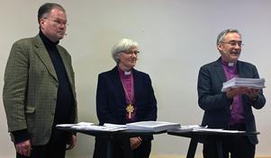 Den 16 mars fick ärkebiskop Antje Jackelén förslaget på reviderad kyrkohandbok i sin hand. Från vänster: Mats Hagelin, kyrkoherde i Simrishamn och vice ordförande i revisionsgruppen, ärkebiskop Antje Jackelén och Esbjörn Hagberg, biskop i Karlstad stift och ordförande i revisionsgruppen