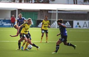 Matilda Johansson försöker ta bollen från en GUSK-spelare.