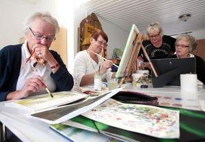 Birgitta Sundberg och Rut Pettersson delar bord, men skapar helt olika bilder. Ett landskap växer fram bredvid en avbild av en tussig pudel.