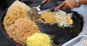 Här förbereds pad thai - populär gatumat i Thailand.