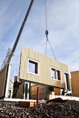 Ännu en vägg lyfts på plats i det nya huset på Juniskärsvägen 180. Här hjälper Kim Mård och Andreas Åström till att få väggen på plats.