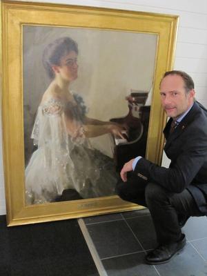 Mikael Gredin, auktionsutropare, med Zorntavlan som fanns med på auktionen.