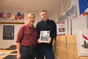 Författaren Kalle Güettler och ordförande i avdelningen Aleksandar Srndovic tillsammans med lådor fulla av den nya boken.