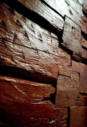 En del av stockarna i den gamla ytterväggen har tidigare använts som innervägg. Det syns på huggmärkena från lerkliningen.