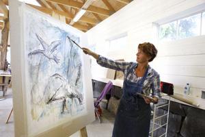 Annelie Björn målar tunna skikt av färg på sin duk. Hon är en av deltagarna på sommarens kurser hos Skaparladan.