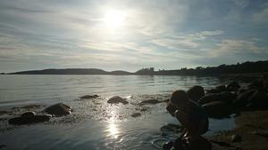 Love tvättar skorna i havet i den vackra solnedgången.