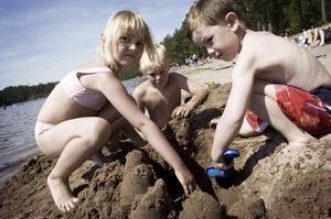 Bro. Felicia, Henrik och Casper bygger en bro i sanden.