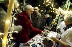 Birgitta Gustafsson provsmakar Ywonne Lindbergs choklad från Bergslagspraliner på julmarknaden i Frövifors pappersbruksmuseum.