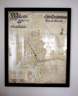 Förr i tiden. En gammal stadskarta över Västerås sitter på väggen. Den visar hur stan såg ut förr. Där är Gardtmanska gården inritad.