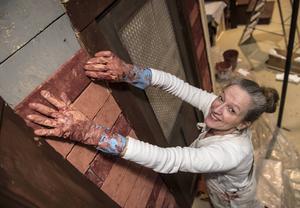 Med hjälp av skumgummi, färg och lim växer tegelväggen fram. – Allt är en illusion, säger Ann Jerbo.