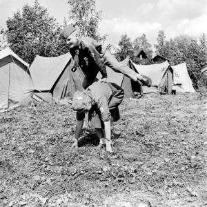 Sommaren 1958 var det scoutläger i Tuna Hästberg och på bilden syns Anders Fredriksson från Borlänge, hoppa bock över lägerchef fru Ingrid Hansson från Mora.