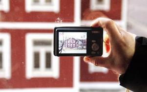 Catarina Larsson, medlem i Grängesbergs Byalag fotograferar stolt det första huset i Källfallet som mer eller mindre är färdigrenoverat. Foto: Andreas Irebring/DT
