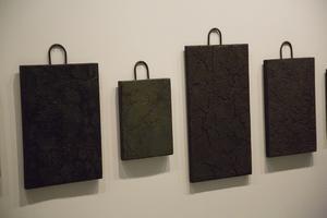 lera. Objekten i serien Spricker som rötter är skapade av papperslera på trä.