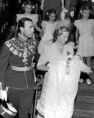 Prinsparet lämnar slottskapellet efter prins Carl Gustafs (blivande Carl XVI Gustafs) dop. Prinsessan Sibylla bär den nydöpte.