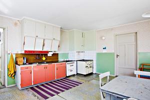 Gammalt kök med vedspis och färgade detaljer.