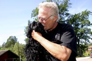 """Hans Carlgren pussar på sin lugna och glada hund Loppan. """"Enda gången hon skäller är när det är någon som ringer på dörren"""". FOTO: Lovisa Granberg"""