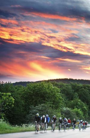 Solen börjar gå upp och himlen skiftar i vackra färger över cyklisterna.