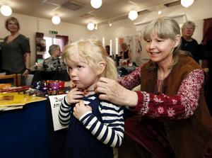 Treåriga Tuva Broström fick ett halsband med vikingapärlor i glas av sin farmor. Siv Olsson som var en av utställarna på Tjejdagen hjälpte henne att sätta på det.