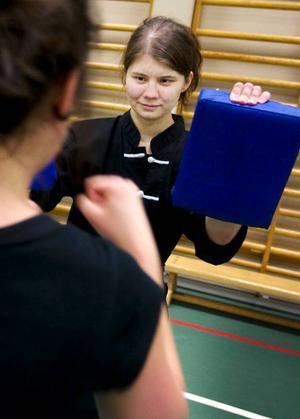 En mits är en vadderad kudde som används att slå och sparka mot. Erika Nilsson håller mitsar för slagövningarna.