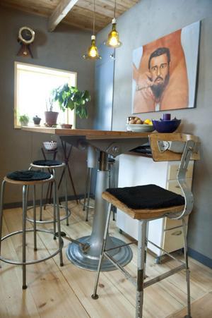 Köket är målad i en mattgrå lerfärg. Glaslamporna som hänger över bordet är gjorda av återvunna vinflaskor och kommer från Återbruket. Castro-tavlan är gåva från Saras man Jörgen.
