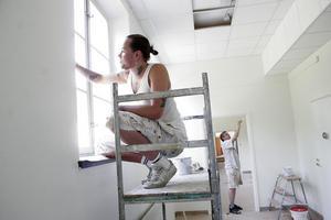 Målaren Robin Johansson på Hudiksvalls Måleritjänst utför slutfinishen i skolkorridoren på första våningen.