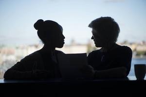 Två kvinnor diskuterar arbete under en fikapaus på jobbet.