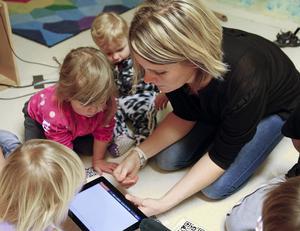 Ida Nordvall visar barn på Kaptenens förskola hur man använder en läsplatta/lärplatta.