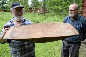 Förutom saker som Hälleforsborna skänkt rensar också hembygdsföreningen bland sina föremål och tar med på auktion. Här ett tråg från minst 1800-talet visar Remy Olsson och Kjell Bäcklund.