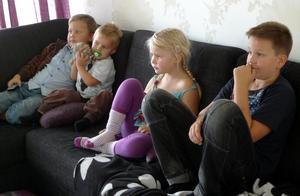 Melker, Albin, Elsa och Herman kollar på TV, tydligen något spännande.