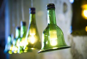 Vinflaskor har förvandlats till lampor. Kapsylerna låter Anny sitta kvar.