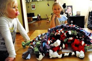 Nora poserar med några av sina hemgjorda hundleksaker, tillsammans med lillasyster Loka.