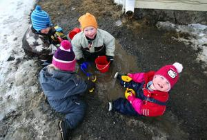 På föräldrakooperativet Ö-barna finns det 13 barn, där sju av barnen kommer från fastlandet. Henning, Selma, Vidar och Amanda leker i vattenpölen.– Det är en bullerby-känsla, en fantastisk miljö för barnen, säger Jonas Welander som är på förskolan och gör en av  sina fyra årliga insatser på förskolan som förälder.