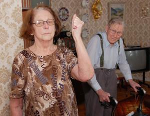 Upprörd. –Vet hut, sjukvårdspolitiker! Elly Larsson, 81 år, är upprörd sedan hennes 89-årige man Bertil, som har svåra ryggsmärtor, fått tillbringa nio timmar i rullstol för att få sina bensår omsedda.