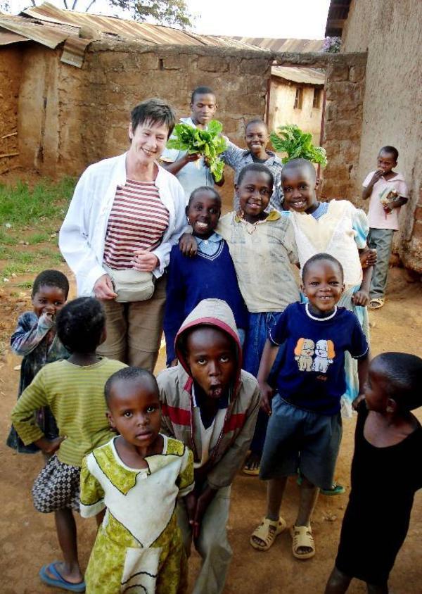 Inger Åsén tillsammans med barn som fått möjligheten att lära sig läsa och skriva på en skola i Kibera Foto: Privat