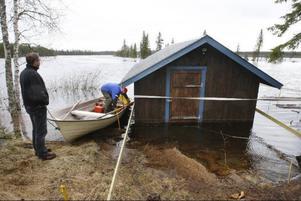 Magnus Löfgren och hans svärfar Jan Olenäs gör sig redo för en båttur på den översvämmade Rönnösjön.