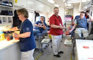 Ruschigt. Det är full fart på det lilla utrymmet i blodbussen. Sjuksköterskan Ove Gefvert tar hand om blodgivaren Kent Sjöberg. På britsen till höger väntar Navdar Hay Yousef som är ny givare. Vid bänken står undersköterskan Lasse Malmberg.