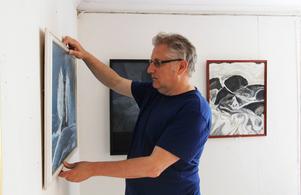 Lasse Arvidsson hänger upp sina tavlor.