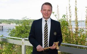 Anders Larsson med klubban som bekräftar att han är ny ordförande i Svenska Ishockeyförbundet.