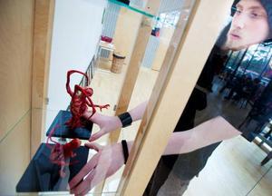 Mikael Wallentin placerar sina plast-skulpturer i ett skyddande skåp.